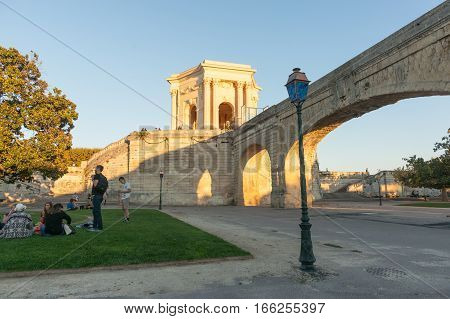 MONTPELLIER, FRANCE - SEPTEMBER 29, 2016; Young people on lawn by aquaduct below Chateau D'Eau or water tower caught in late sun on Promenade du Peyrou Montpellier France Roman urban architecture