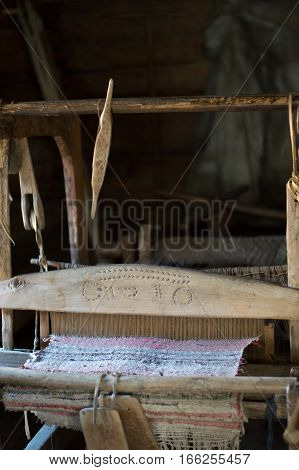 Close up of an antique wooden loom with woven fabric. The beater is hand carved. A shuttle is hanging from the top of the loom. Photographed in Taltsy Museum, Siberia, Russian Federation.