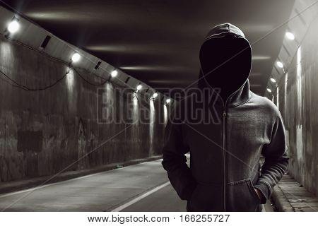 Hacker standing alone in the underground tunnel