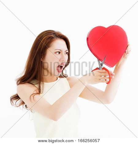 angry woman cutting the heart shape by scissors