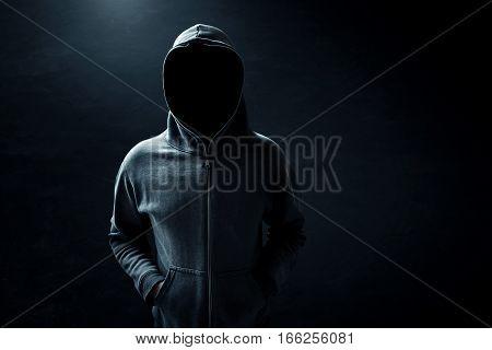 Unknown hacker standing alone in dark room