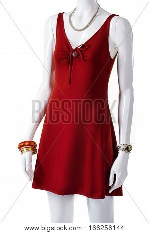 Short red dress with accessories. Female mannequin wearing attractive garment. Red dress and gold bracelets. Nice casual clothing for ladies.