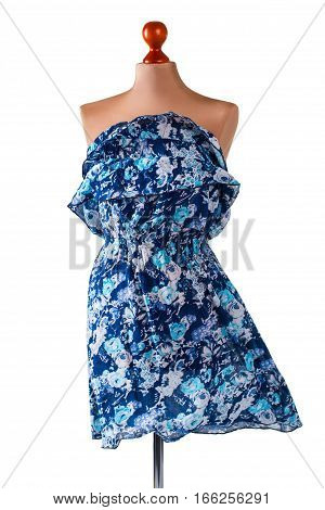 Casual blue floral dress. Blue dress on armless mannequin. New garment in fashion boutique. Strapless dress in the wind.