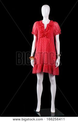 Red v-neck summer dress. White mannequin in red dress. Lady's clothing on black background. Seasonal offer at fashion store.