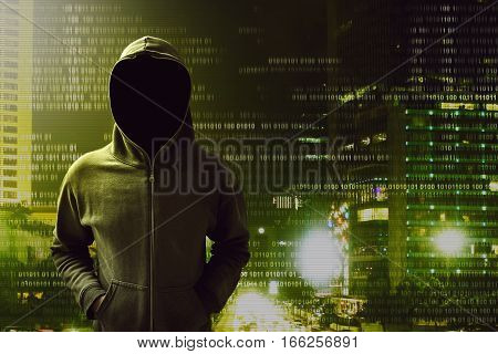 Hacker standing over a screen with binary code
