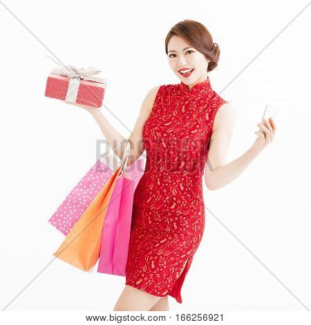 young chinese woman holding shopping bags and smart phone