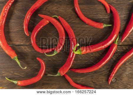 Red hot chili peppers, shot from above on a dark brown wooden texture
