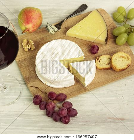 A square photo of a tasting with a glass of red wine, different types of cheese, bread, nuts, pear, grapes, on a wooden board with copyspace