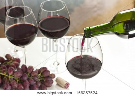Photo of red wine being poured into glass from bottle, with more blurred full wine glasses in the background, and also out of focus grapes and cork