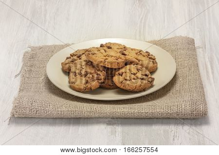 A photo of chocolate chips cookies on a plate, shot on a burlap and light wooden background texture, with copyspace