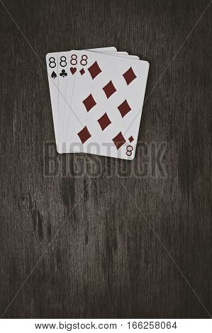 playing cards four eights on a wooden table. space for text. v