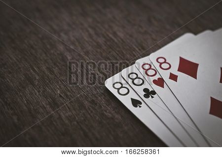 playing cards four eights closeup on a wooden table. space for text. copyspace.
