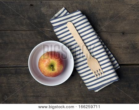 Apple in a Bowl with fork and napkin on a rustic wooden table
