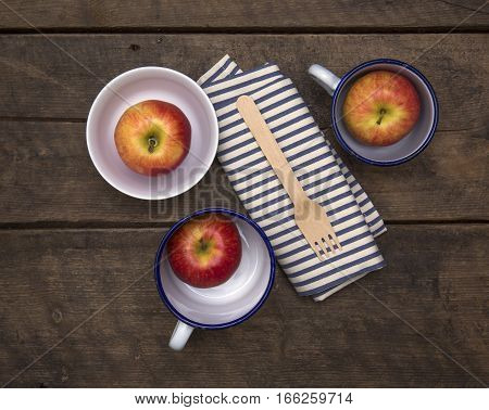 Apples in Bowls with fork and napkin on a rustic wooden table