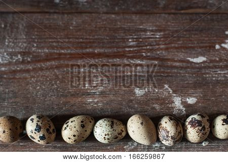 Quail eggs on wooden table flat lay. Top view on rustic background with line of raw eggs, free space for text. Easter, culinary, recipe, healthy food concept