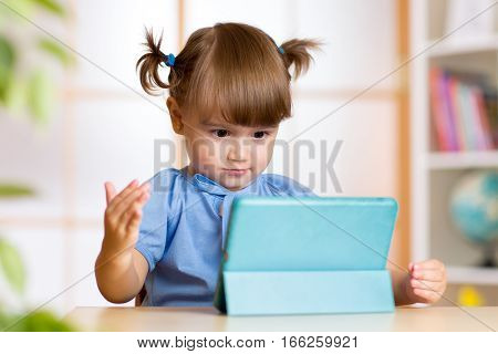 Surprised little girl and her magic tablet