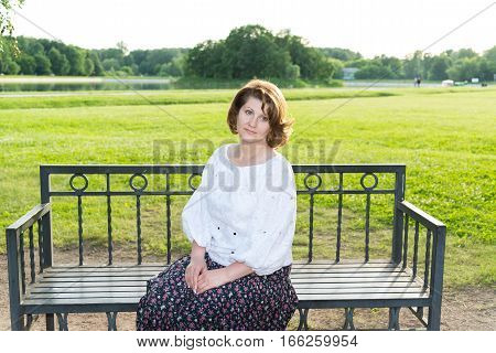 A woman sitting on a bench in the summer park
