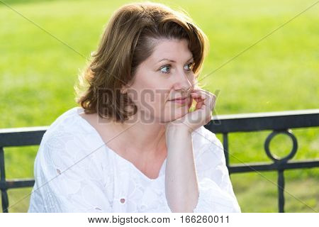 Cheerless woman in a park on a bench