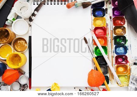 Creative artist workplace flat lay, mockup. top view on table with blank sketchbook, pencils, paintbrushes and dye palettes. Art, workshop, painting, drawing, craft, creativity concept