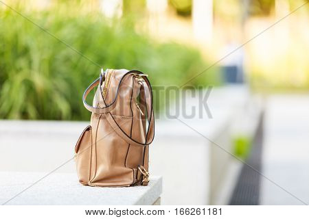 Student fashion concept. Little light brown backpack standing on white ledge outside with green bushes in background