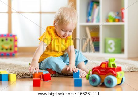 A kid boy playing toy blocks inside his house