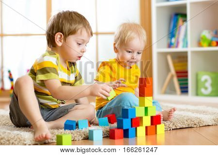 Children toddler and preschooler boys play toy blocks at home or nursery