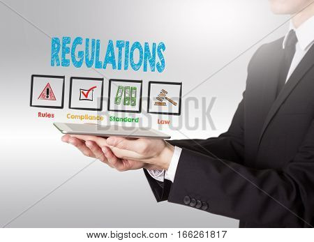 Regulations concept, young man holding a tablet computer.