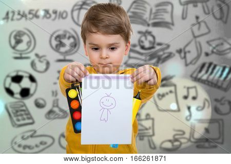 Little boy holding his first drawing in hands.
