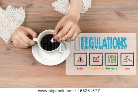 Regulations. Coffee cup top view on wooden table background.