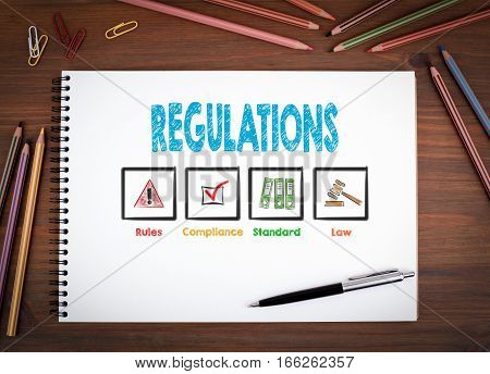 Regulations. Notebooks, pen and colored pencils on a wooden table.