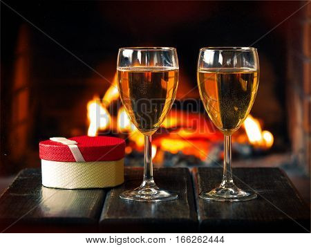 Two glasses of wine and a gift box in the shape of a heart on the background of the fireplace
