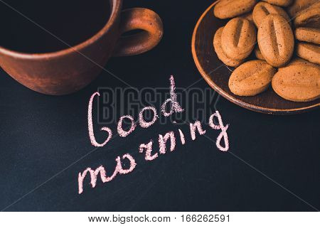 Cup of Coffee and Cookie or Biscuit on a Dark Background. Inscription Good Morning. Selective Focus. Top View.