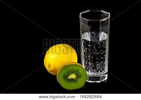 Kiwi lemon and a glass of mineral water on black background close-up.
