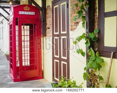 Red telephone box in street with historical architecture in Ipoh Malaysia