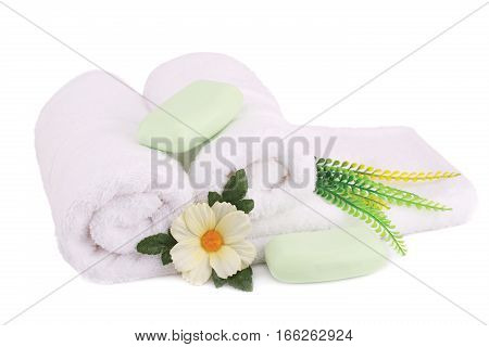 White rolled towels with soaps and flowers isolated on white background.