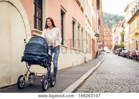 Young mother taking her baby out to the city, enjoying a happy time in Heidelberg, Germany.