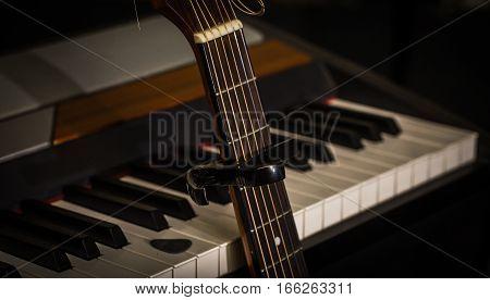 Musical Instruments Piano Keys And Acoustic Guitar Capadaster