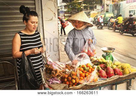 Ho Chi Minh Vietnam Januar 15 2017: Unidentified vietnamese woman bye fruit on market place in Ho Chi Mihn city Vietnam Januar 15 2017.