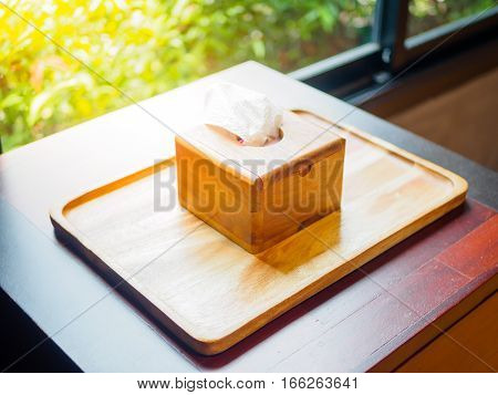 tissue paper in wooden box holder on wooden tray and floor