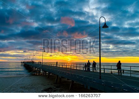 People walking on Glenelg Beach jetty at sunset South Australia