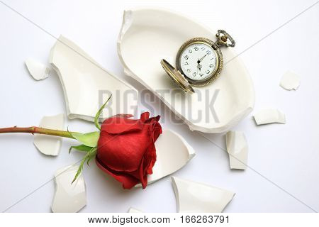 Red Rose and pocket watch laying on a broken bowl