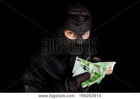 Masked Thief In Balaclava With Stolen Money Isolated On Black