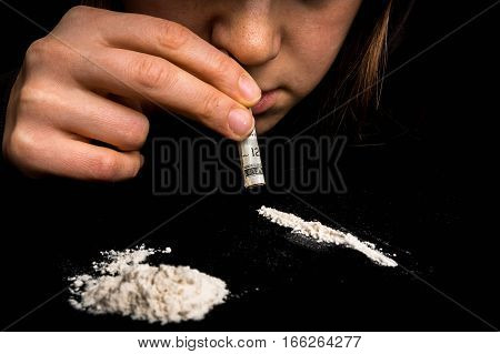 Junkie woman snorting cocaine powder with rolled banknote on black background poster