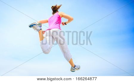 young woman jogging, isolated in front of blue sky