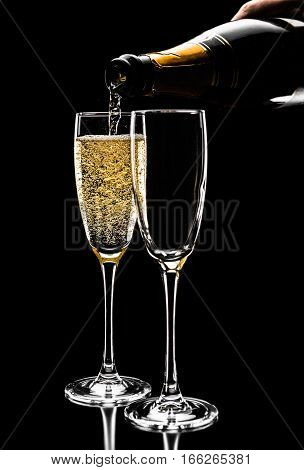 Mans Hand Pours Champagne From Bottle Into Glass, Close Up