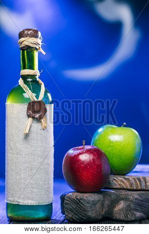 Sealed bottle of white wine and apples on rustic serving boards in mysteriuos blue light
