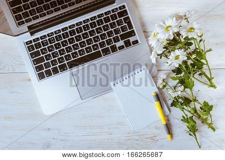 work office wooden desk with laptop, notebook, pen, flower
