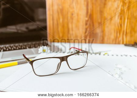 table with laptop glasses pen laptop flowers on wooden table