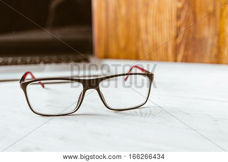 table with laptop glasses laptop on wooden table