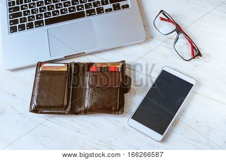 laptop wallet glasses phone on wooden table